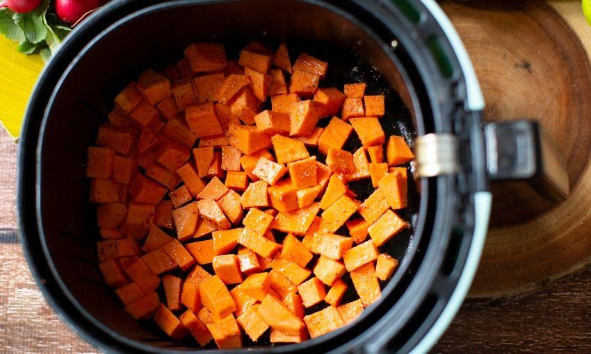 adding sweet potato chunks to air fryer