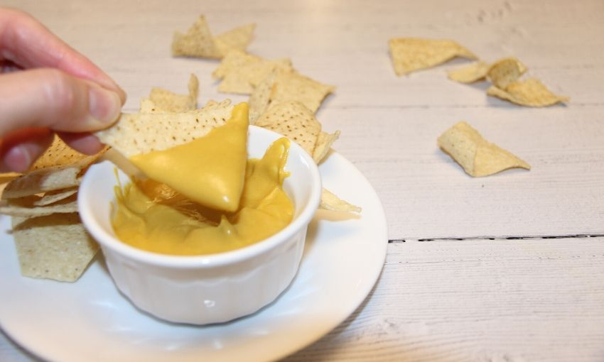 dipping chip in vegan queso recipe